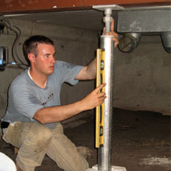 A contractor in Clark Fork installing a crawl space jack post.