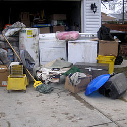 Soaked, wet personal items sitting in a driveway, including a washer and dryer in Veradale.