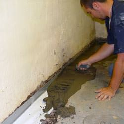 A basement waterproofer installing a perimeter drain system in Liberty Lake