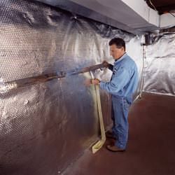Installation of a radiant heat and vapor barrier on a basement wall in Fairchild Air Force Base